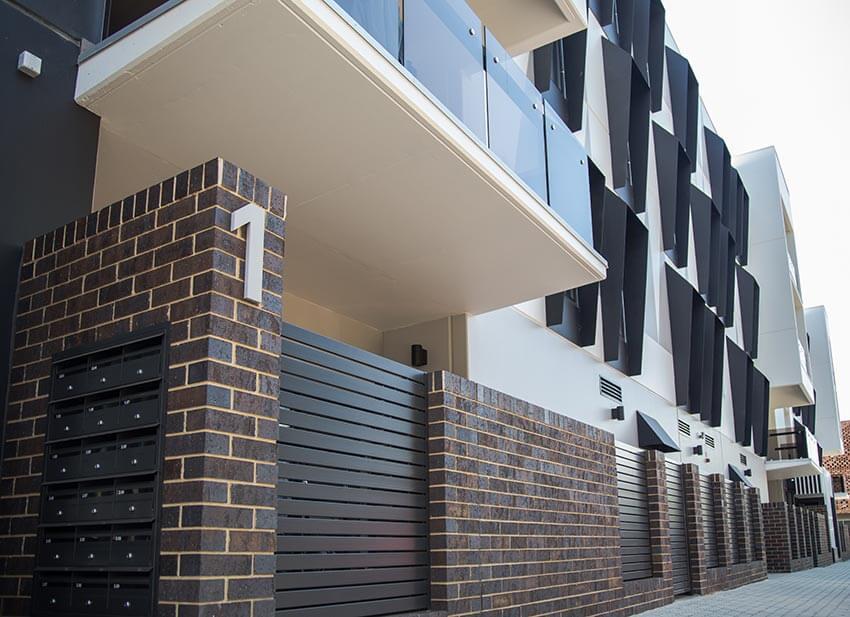 Bowden Coachhouse Dark Brick On Modern Apartment Building Wall 5